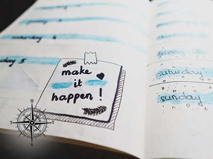 """Day-timer with a note on it that says """"Make it happen!"""""""