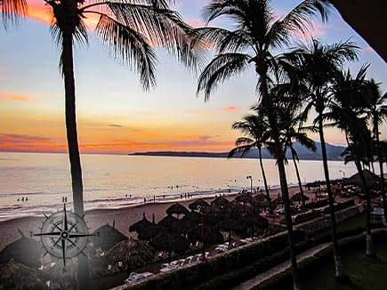 Beach sunset with palm trees and sun chairs in Puerto Vallarta, Mexico