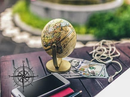 Small globe, money phone and headphones on a table